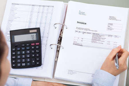 Close-up Of Businessperson Working With Document And Calculator photo
