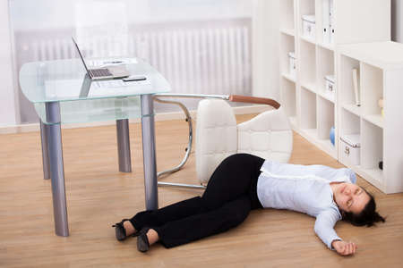 Exhausted Businesswoman Fainted On Floor At Workplace Stock Photo