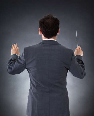 Male Orchestra Conductor Directing With Baton Over Black Background