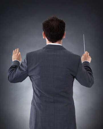lead: Maschio Orchestra Conductor Direzione Con Baton Su Sfondo nero