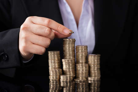 Close-up Of Businesswoman Putting Coin To Rising Stack Of Coins photo