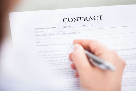 Close-up Of Hand Holding Pen On Contract Form photo