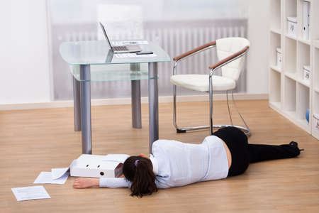 exhausted: Exhausted Businesswoman Fainted On Floor At Workplace Stock Photo