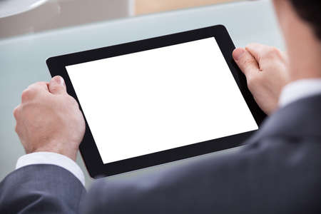 Close-up Of Businessman Looking At Digital Tablet photo