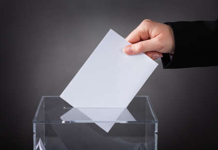 ballot box: Close-up Of Hand Putting Ballot In Glass Box