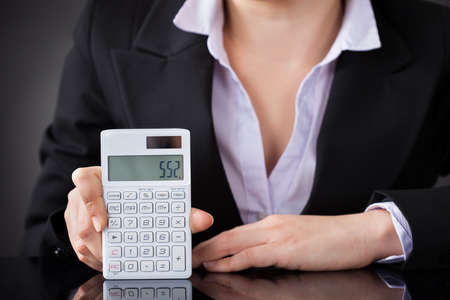Close-up Photo Of Business Person Using Calculator photo