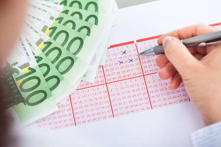 loteria: Primer plano de la mano con la pluma de marcado en el boleto de la Lotería y de billetes