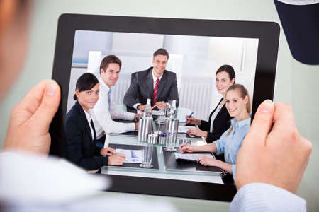 conference room meeting: Close-up Of Businessperson Looking At Video Conference On Digital Tablet