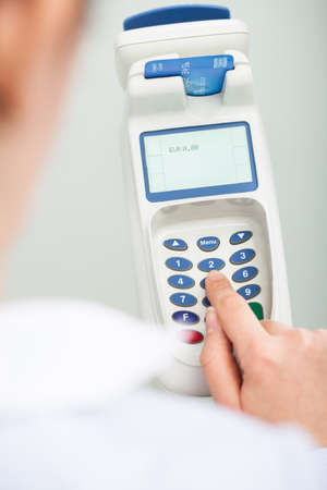 chip and pin: Close-up Of Person Using A Credit Card Reader