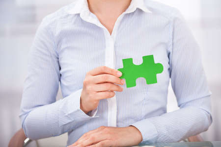Close-up Of Business Person Showing Green Puzzle photo