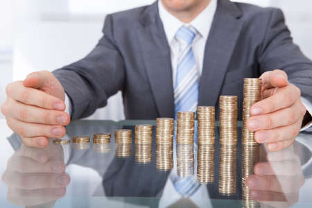 ビジネスマンのクローズ アップのビジネスのためのコイン スタックを保護します。 写真素材