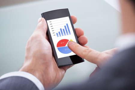 Close-up Of Businessperson Looking At Graph On Mobile Phone photo