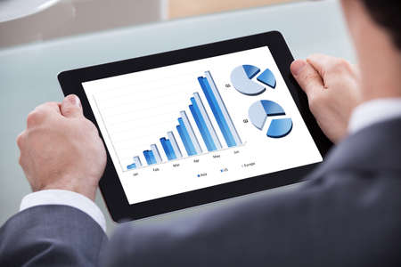 Close-up Of Businessman Analyzing Chart On Digital Tablet photo
