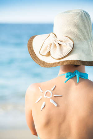 Rear view of young woman with sun drawn from sunscreen on back at beach Stock Photo
