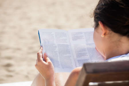 Rear view of woman reading book on deck chair at beach photo