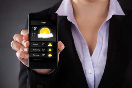 forecast: Close-up Of Businessperson Showing Weather Forecast On Mobile Phone