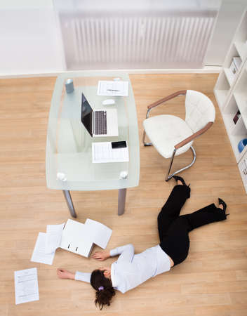 modern chair: Exhausted Businesswoman Fainted On Floor At Workplace Stock Photo