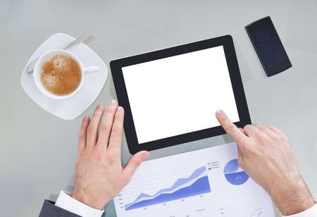 Businessperson Hand Holding Blank Digital Tablet With Coffee Cup And Chart On Table photo