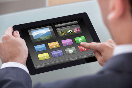 Close-up Of Businessperson Hand Over Icons On Digital Tablet photo