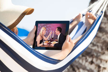 holiday movies: Woman watching movie on digital tablet while relaxing in hammock at beach Stock Photo