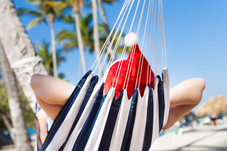 Thoughtful young woman wearing Santa hat in hammock at beach photo