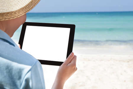 Cropped image of woman using digital tablet at beach photo