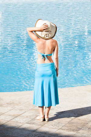 Full length rear view of woman standing at poolside photo