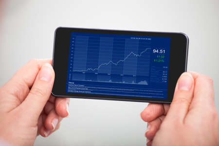 Close-up Hand Holding Mobile Phone With Financial Graph photo