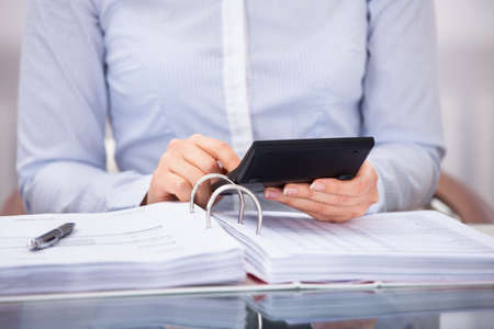 Close-up Of Businessperson Checking An Invoice On Calculator At Desk photo