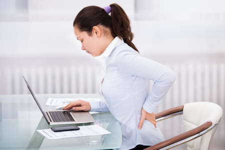 Young Businesswoman Having Back Ache Sitting In Front Of Laptop photo