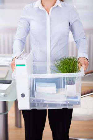 Close-up Of Businessperson Carrying Office Supply In Plastic Container photo