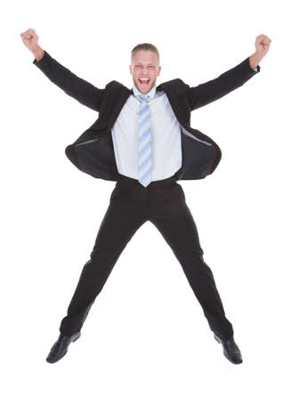 exultant: Exultant stylish young businessman in a suit jumping and raising his fists in the air as he celebrates a success full length isolated on white Stock Photo