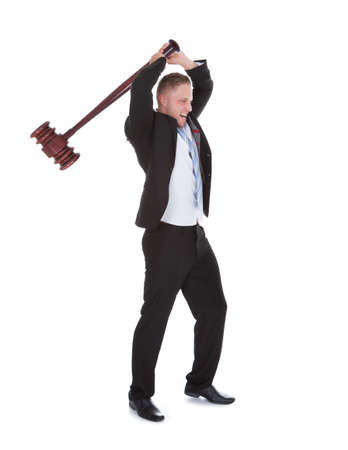 retribution: Businessman wielding a big wooden mallet holding it above his head with both hands about to smash it downwards  isolated on white