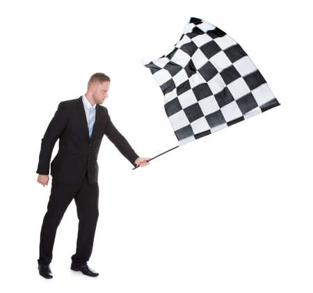 Conceptual image of a stylish young businessman waving a black and white checkered flag as used to signal the successful completion of a race in motor sport  isolated on white Stock Photo