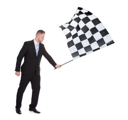 bandera carrera: Imagen conceptual de un hombre de negocios con estilo joven con una bandera a cuadros en blanco y negro como se utiliza para indicar la finalización con éxito de una carrera en el deporte de motor aislado en blanco Foto de archivo