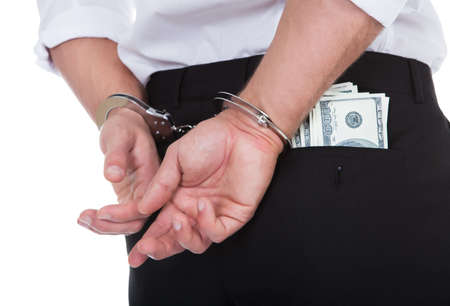 proceeds: Primer punto de vista de detr�s de un hombre esposado con billetes de d�lar en el bolsillo conceptual de la delincuencia y la corrupci�n con un soborno el bot�n o un pago Foto de archivo