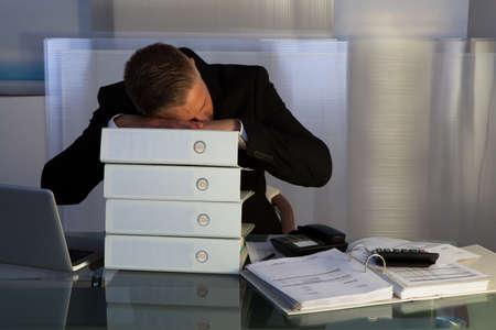 cansancio: Hombre de negocios agotado que duerme un una pila de archivos mientras se trabaja hasta tarde en la oficina durante la noche, mientras trata de cumplir con un plazo para la mañana