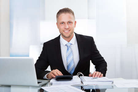 Smiling successful businessman sitting st his desk in the office surrounded by paperwork using a calculator and a laptop photo