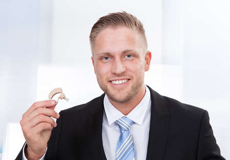 Photo of the businessman holding hearing aid photo
