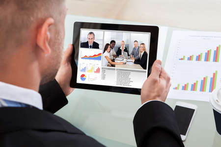 conference call: Businessman on a video or conference call on his tablet with an image of work colleagues in a meeting and bar graphs on the screen