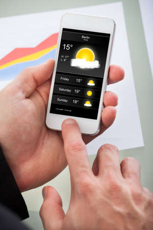 weather forecast: Man checking the weather forecast for the day on an application on his mobile phone  view of the screen with a cloudy sunny day