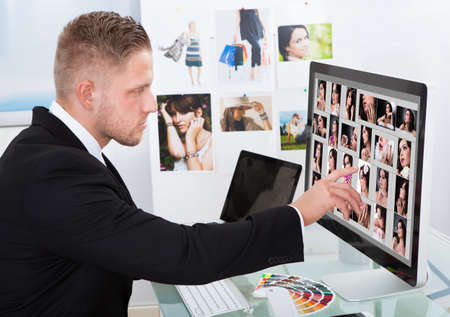 image editing: Businessman sitting at his desk in front of a large screen monitor editing photographs Stock Photo