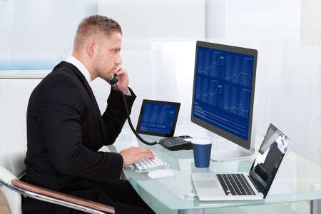 彼は彼の携帯電話の呼び出しを取ると同時にコンピューターの画面に取り組んで彼の机で勤勉なビジネスマン