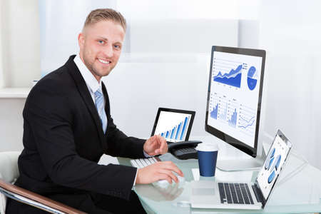 Businessman with good performance graph sitting at his desk with statistical reports spread over three monitors cheering and clasping his fists photo