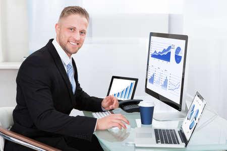 Homme d'affaires avec un bon graphique de la performance assis à son bureau avec des rapports statistiques, réparties sur trois moniteurs encourager et serrant les poings