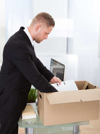 belongings: Businessman moving offices packing up all his personal belongings and files into a brown cardboard box