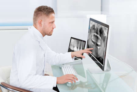 Doctor or radiologist looking at an x-ray online displayed on a desktop monitor as he makes a diagnosis or checks prognosis