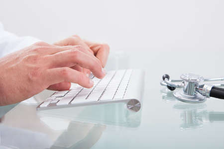 Conceptual medical and healthcare image with a close up of a stethoscope lying on a doctors desk with the hands of the doctor visible behind working on a computer photo
