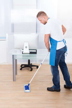 disinfect: Handsome male janitor or cleaner cleaning the floor in an office building using a mop to wash the and disinfect the surface