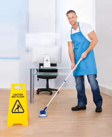 mopping: Yellow warning notice to caution people to a slippery wet surface as a janitor mops the floor in an office building